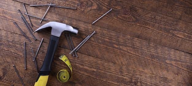 Martelo de ferro, fita de centímetro e pregos na mesa de madeira