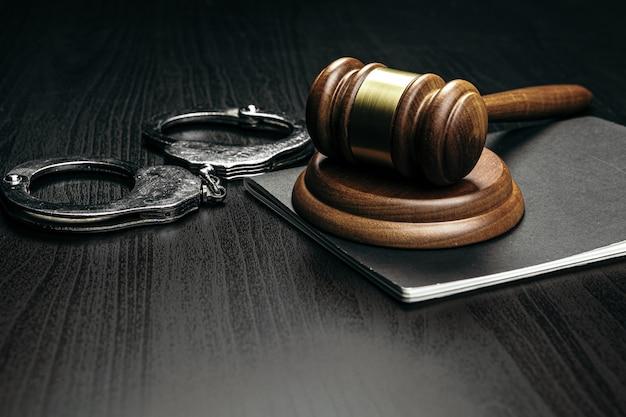 Martelo de juiz com algemas na mesa de madeira