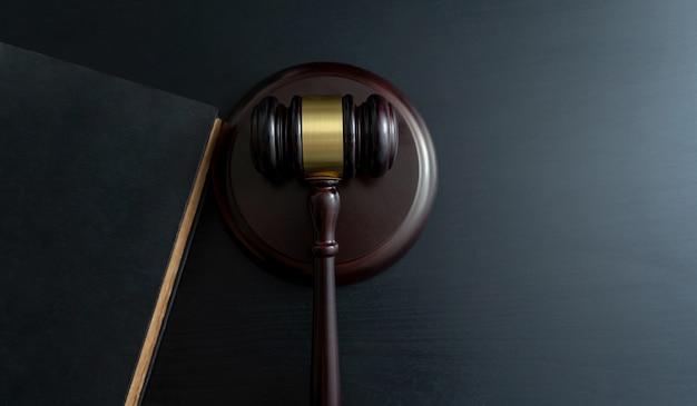 Martelo de juiz com livros na mesa de madeira