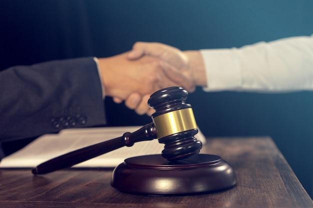 Martelo de juiz com os advogados da justiça, tendo reunião de equipe