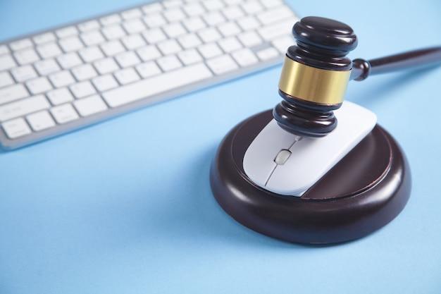 Martelo de juiz com um mouse e teclado de computador.