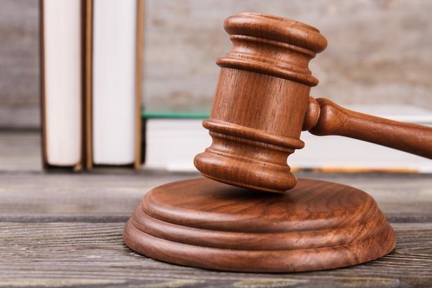 Martelo de juiz de madeira de close-up. livros de direito em segundo plano.