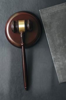 Martelo de juiz de madeira e livro na mesa superior de couro preto.