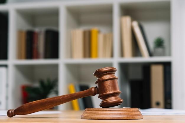 Martelo de juiz de madeira na mesa em frente a estante