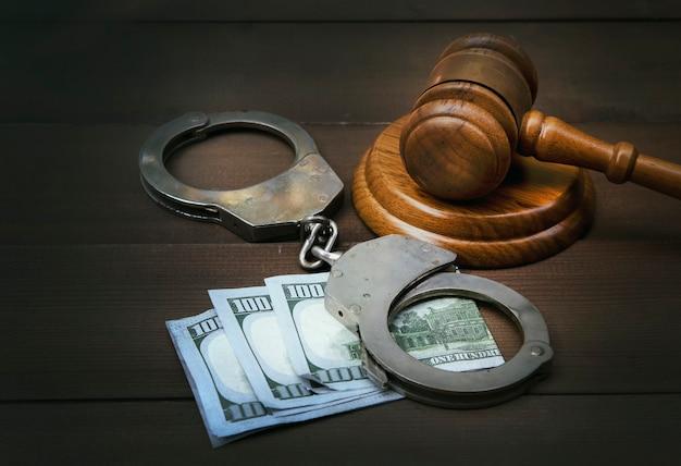 Martelo de juiz e algemas com notas de dólares na mesa de madeira