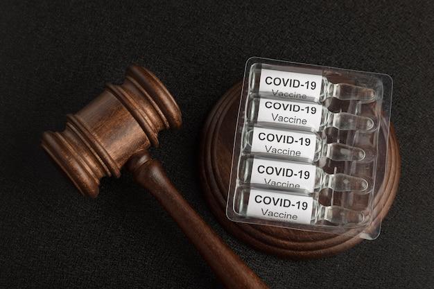 Martelo de juiz e ampolas com letras covid19