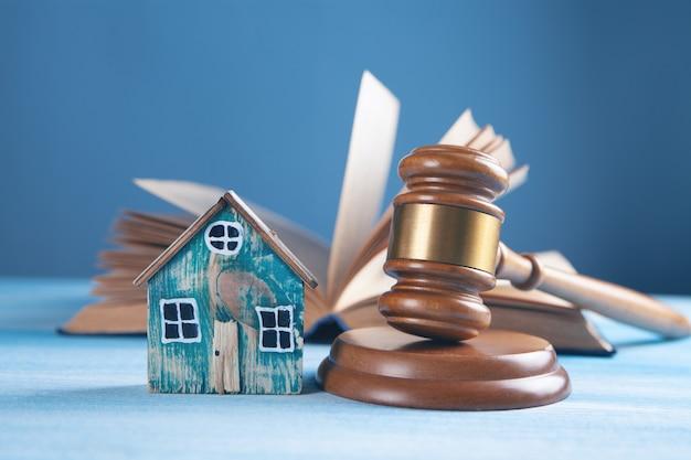 Martelo de juiz e casas em uma superfície de madeira