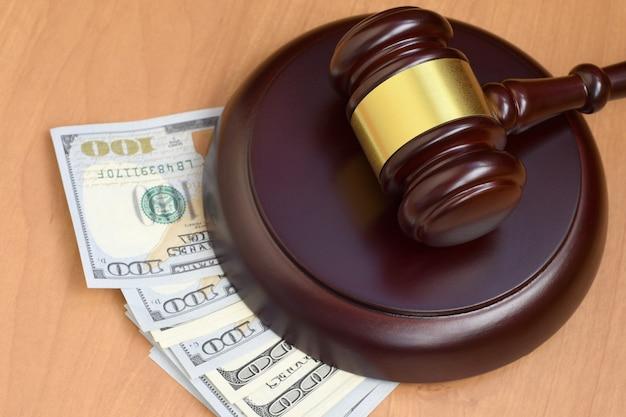 Martelo de juiz e dinheiro na mesa de madeira marrom
