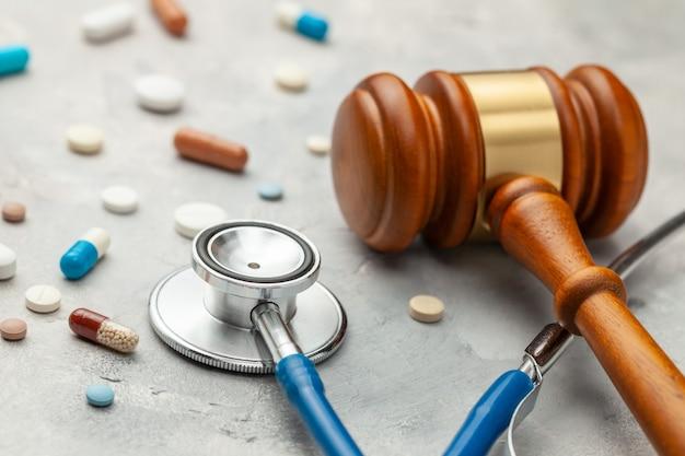 Martelo de juiz e estetoscópio com comprimidos. a lei da medicina, a sentença por negligência médica.
