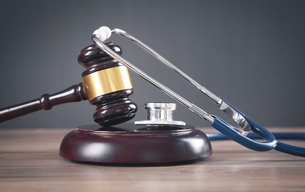 Martelo de juiz e estetoscópio na mesa de madeira.