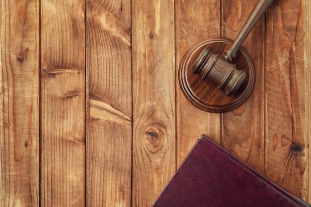 Martelo de juiz (martelo de leilão) e livro na mesa
