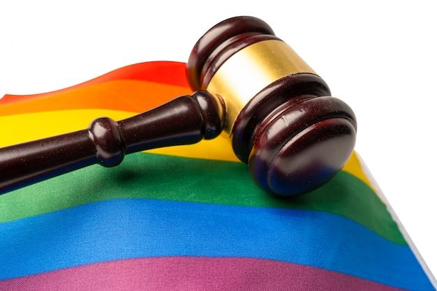 Martelo de juiz na bandeira do arco-íris, símbolo do mês do orgulho lgbt.