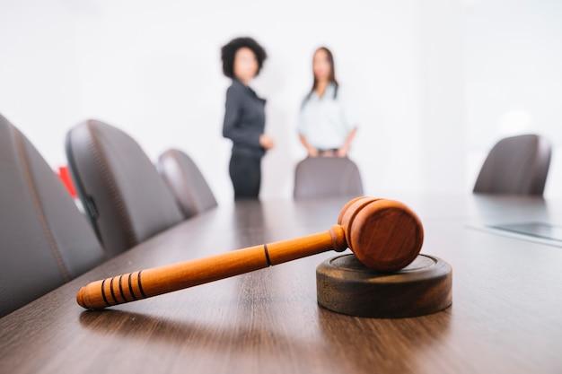 Martelo de juiz na mesa e mulheres afro-americanas no escritório