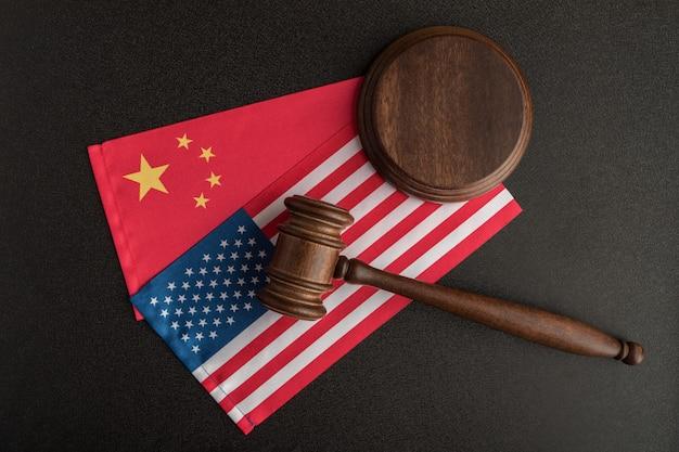 Martelo de juiz sobre as bandeiras americanas e chinesas