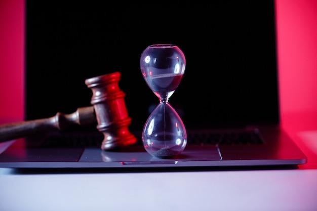 Martelo de juízes, balança de justiça e ampulheta no laptop.