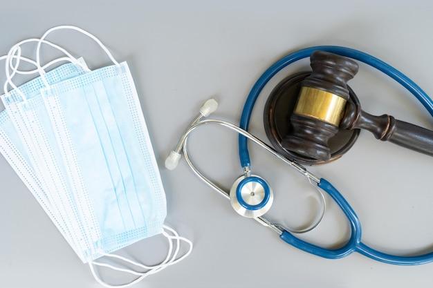 Martelo de lei, estetoscópio e máscaras antivírus, conceito de direito médico