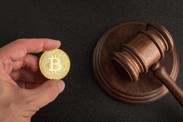 Martelo de lei ou leilão e bitcoins na mão. resolução de disputas sobre fraudes em bitcoin. legislação sobre criptomoeda.