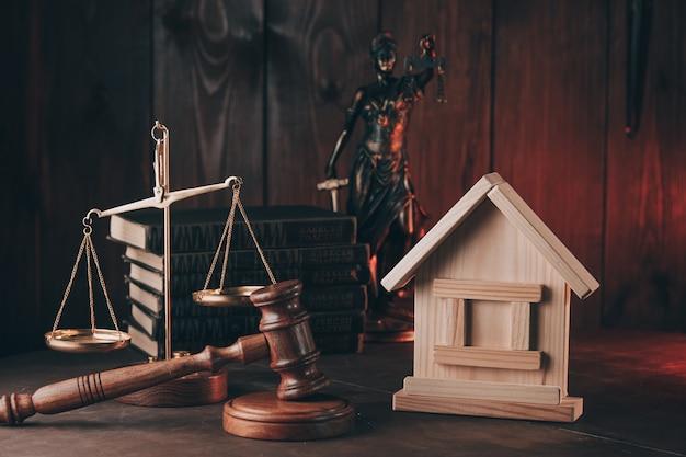 Martelo de leilão e pequena casa sobre a mesa, leilão de hipotecas imobiliárias