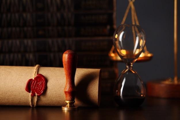 Martelo de madeira, ampulheta, livros e carimbo no testamento e a última vontade em quarto escuro.