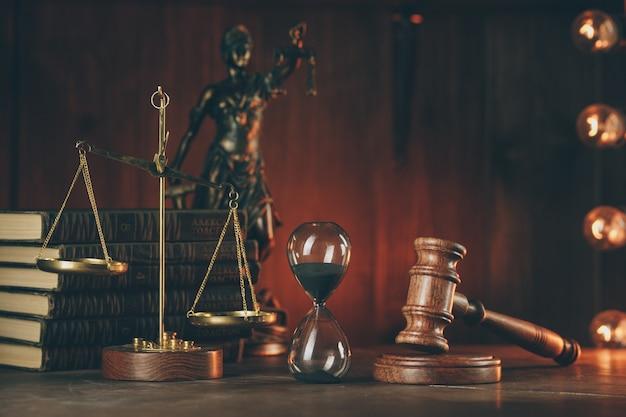 Martelo de madeira, ampulheta, livros e senhora da justiça em quarto escuro. ferramentas notariais