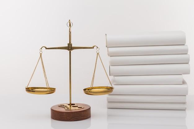 Martelo de madeira com escalas de justiça e livro aberto, isolado no branco.