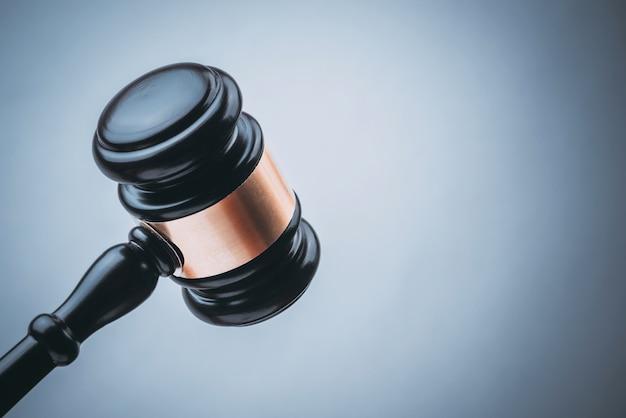 Martelo de madeira de juiz preto com fundo azul