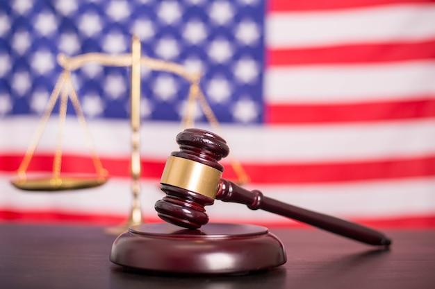 Martelo de madeira do juiz, escalas douradas da justiça com fundo preto