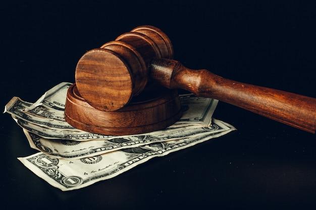 Martelo de madeira do juiz no close up das notas de banco do dólar americano. conceito de corrupção de justiça