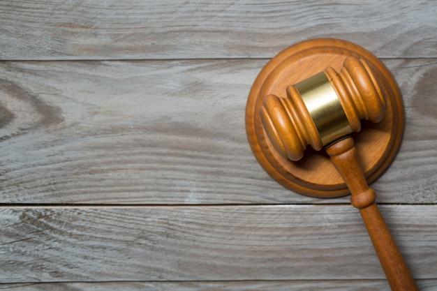 Martelo de madeira do martelo do juiz no fundo de madeira da tabela.