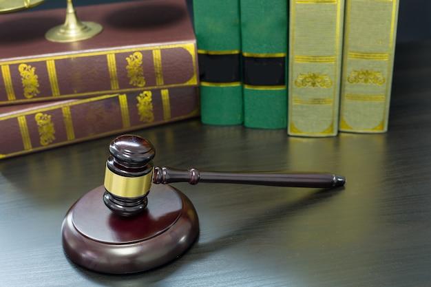 Martelo de madeira dos juízes, dourado escalas justiça com fundo preto.