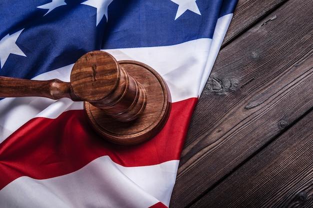 Martelo de madeira e bandeira eua na tabela close-up