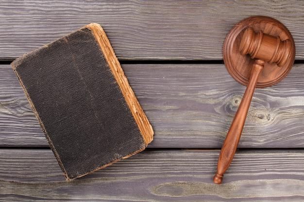 Martelo de madeira e livro de leis antigas.