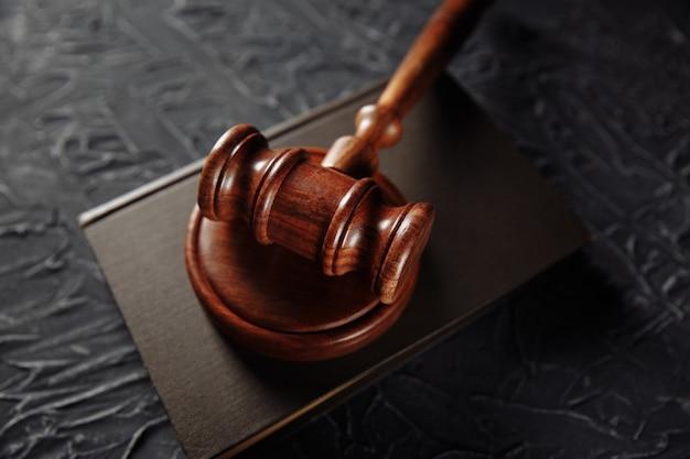 Martelo de madeira e livro jurídico em uma mesa.