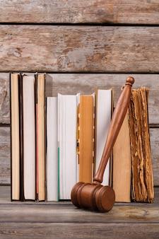 Martelo de madeira e livros antigos. martelo de juiz de madeira de tiro vertical e livros envelhecidos tiro vertical.