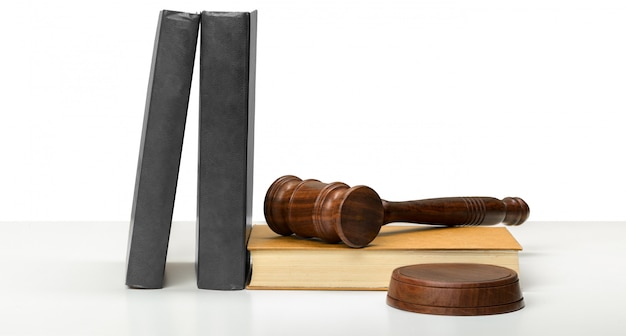 Martelo de madeira e livros na mesa de madeira