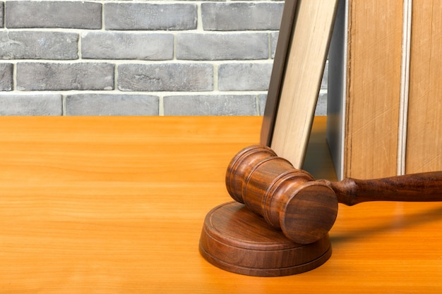 Martelo de madeira e livros sobre a mesa de madeira
