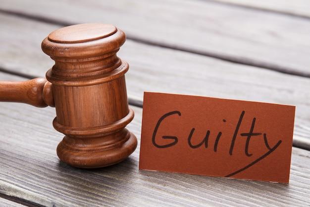 Martelo de madeira e palavra culpada. martelo do juiz na mesa.