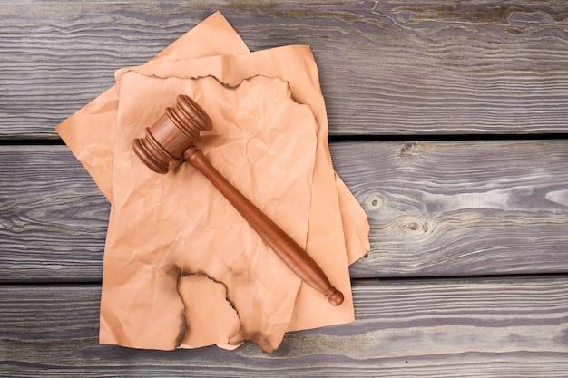 Martelo de madeira em papéis bege.