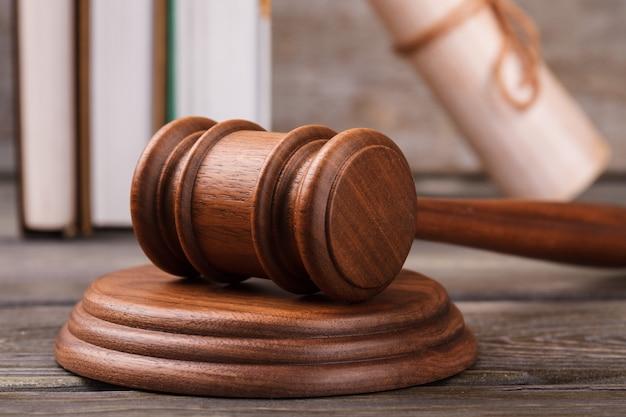 Martelo de madeira marrom de close-up. livros de direito em segundo plano.