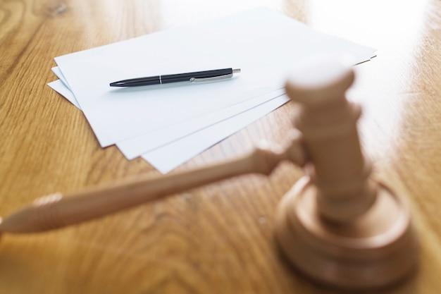 Martelo de madeira na frente da caneta e papéis em branco