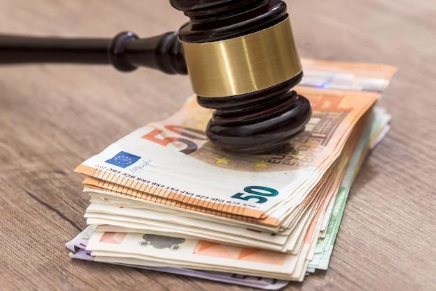Martelo de madeira nas notas de euro close-up