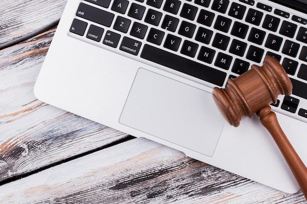 Martelo de madeira no teclado de um laptop. mesa de madeira branca velha.