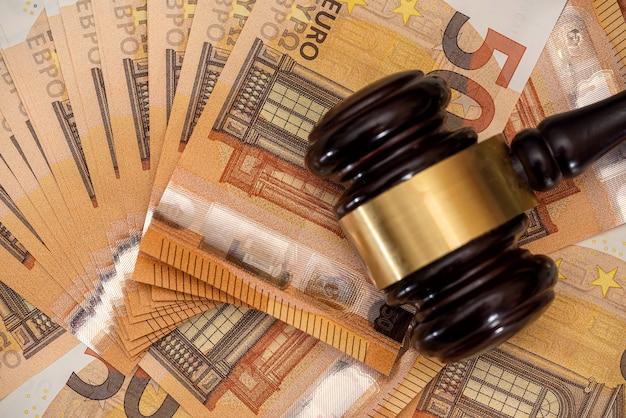 Martelo de madeira para advogado do juiz em contas de 50 euros, conceito de corrupção e suborno.