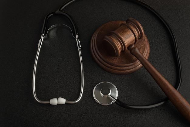Martelo de martelo de juiz e estetoscópio na superfície preta. direito e medicina. sentença por negligência médica.