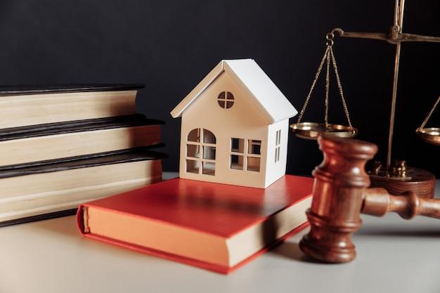 Martelo de modelo de casa de leilão de juiz e conceito imobiliário e livros de direito