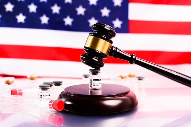 Martelo do judiciário nas farmácias que vendem vacina contra coronavírus, com bandeira americana desfocada