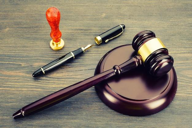 Martelo do juiz, caneta-tinteiro e um carimbo em uma velha mesa de madeira