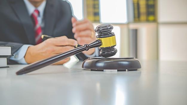 Martelo do juiz com advogados de justiça, tendo uma reunião de equipe no fundo do escritório de advocacia. conceitos de direito e serviços jurídicos.