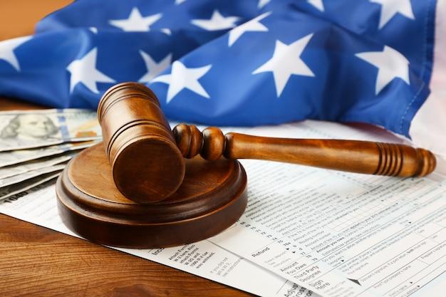 Martelo do juiz com formulário de declaração de imposto de renda individual e bandeira americana na mesa de madeira