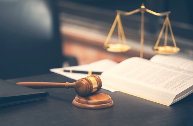 Martelo do juiz com livro de direito na mesa de madeira e balança de justiça, conceito de advogado